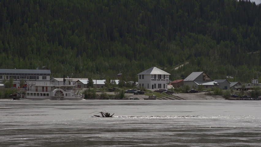 Dawson City, YT, Canada - July 2013:A near-replica of a Yukon River paddlewheeler plies the swirling current of the Yukon as it pushes its way upstream past Dawson City, Yukon Territory, Canada.
