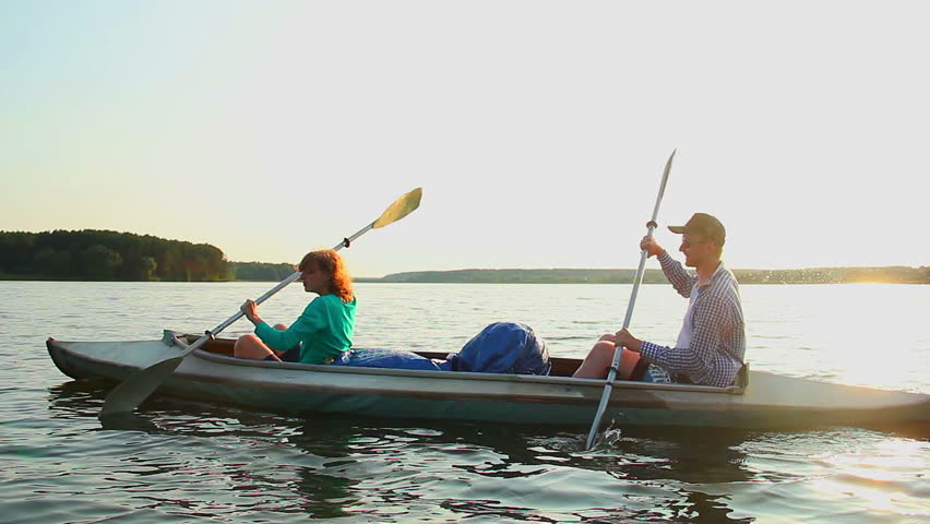 Young positive couple paddling kayak at sunset, beautiful view. Active people canoeing along river, healthy leisure outdoors, sport. Peaceful recreation, doing fitness together, summer adventure