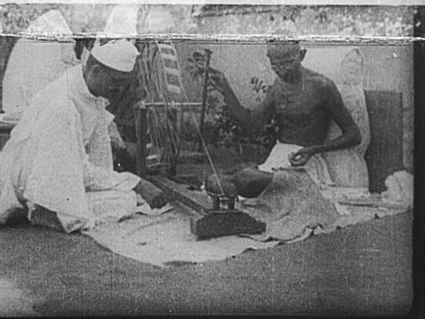 INDIA- CIRCA LATE 1920's: Gandhi spins yarn, assisted by a man in a topi and mundu. Children look on, holding yarn in their hands.