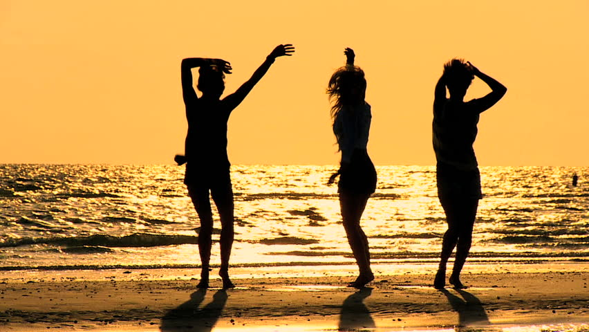 Three carefree girls dancing on the beach at sunset in silhouette 60 FPS