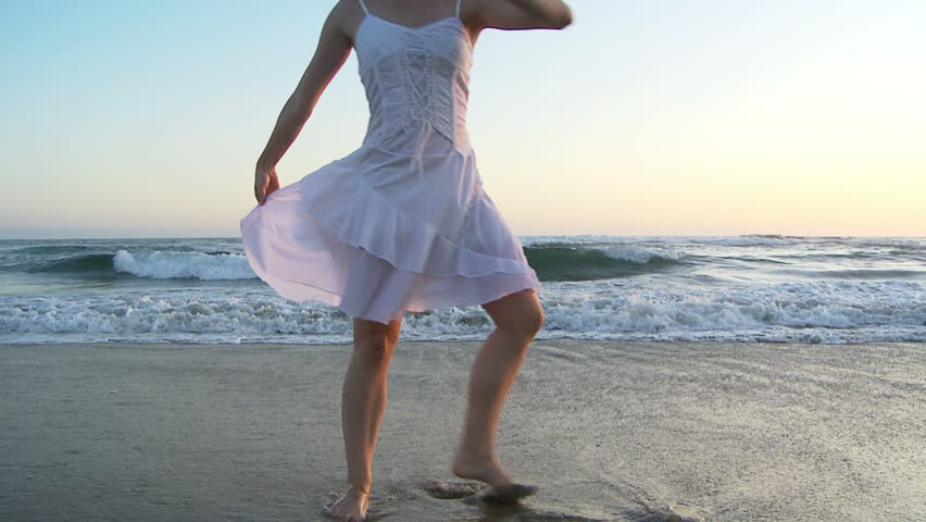Young woman doing ballet at the beach