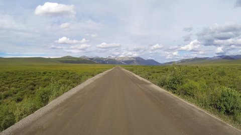 Driving plate/pov shot of the Dempster Highway in a mostly straight, open expanse of Yukon Territory, Canada, heading north.
