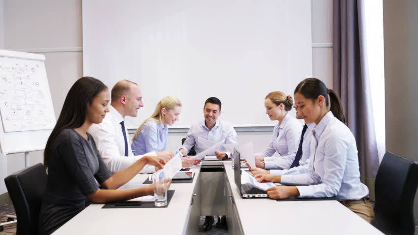 Business, teamwork, people and technology concept - smiling business team with laptop computer, papers and smartphone making thumbs up gesture in office | Shutterstock HD Video #7902121