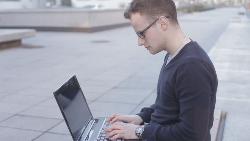 Young student sitting on a bench with laptop computer on a city background. | Shutterstock HD Video #7919221