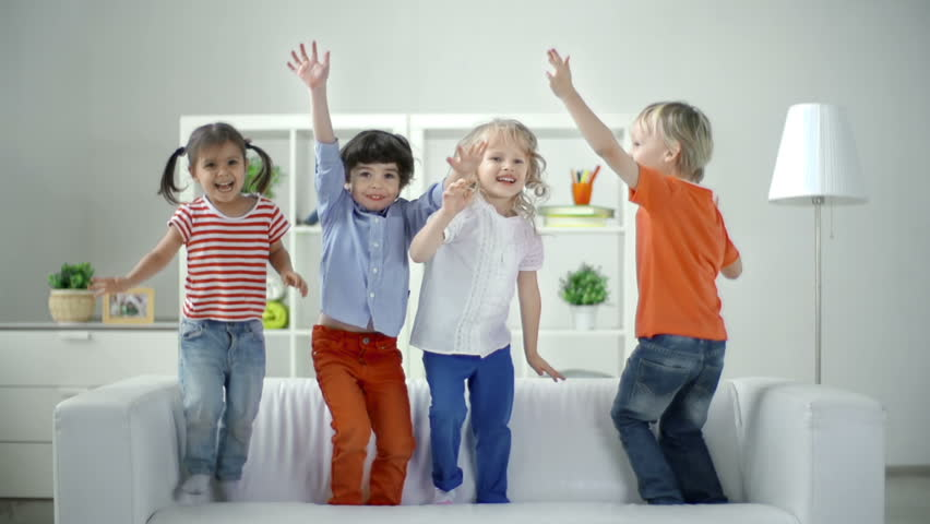 Real time video turning into slow motion of four little friends having fun leaping on the sofa