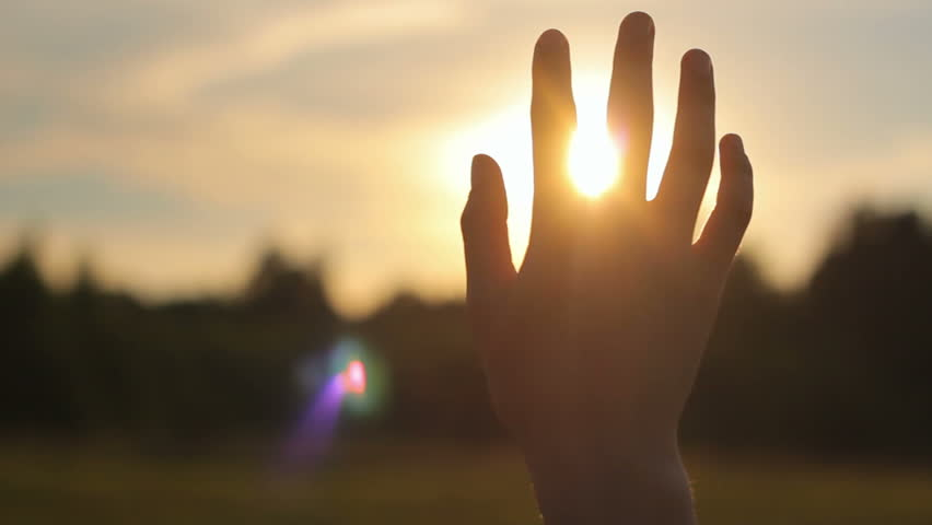 Close-up of raised hand in the sky against the sun in nature, religion, spirituality, camera movement | Shutterstock Video #7927471
