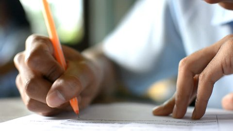 close up a hands of student during the exam in the classroom