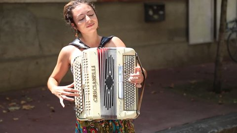 TOULOUSE, FRANCE - JULY 2014: Young woman playing the accordion in the streets of Toulouse. Playing street music, also known as busking, is popular in many cities in France.
