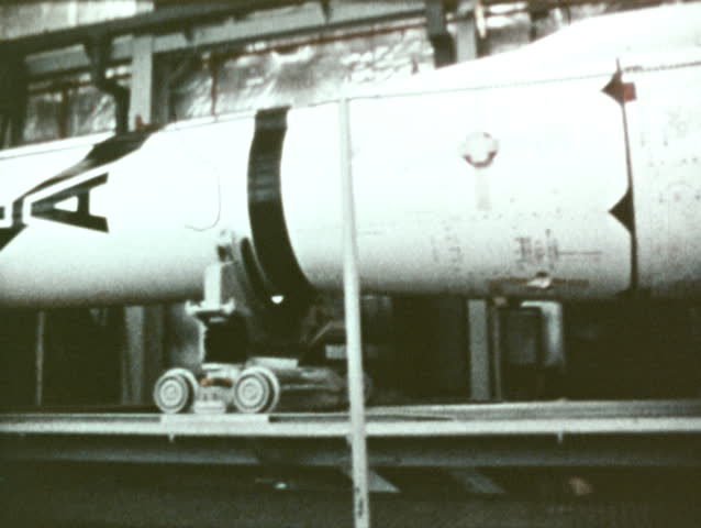 CIRCA 1972: An Italian rocket inside a warehouse. A small launch site early in the morning. An open water launch site.  A rocket launches from the open water site during the night.