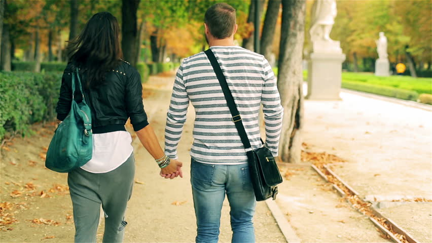 Couple walking in park and holding hands at autumn, steadycam shot