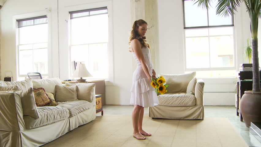 Woman dancing in living room with sunflowers