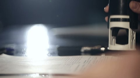 Close up of female hand that puts a stamp in the contract or documents. Slow motion