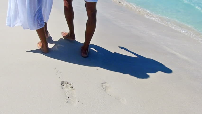 Rear view of happy, young couple walking along the tropical beach.Slow motion, high speed camera