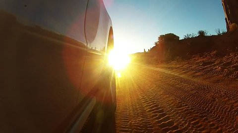 Monument Valley, Drive thru desert canyon in USA at sunset against bright setting sun with lens flare
