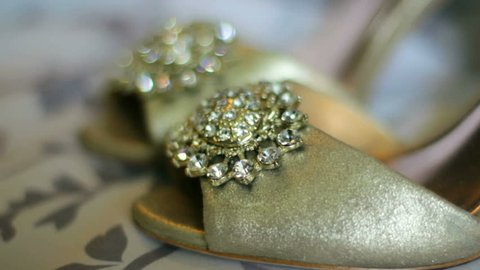 Close up of a brides wedding shoes displayed on a bed.