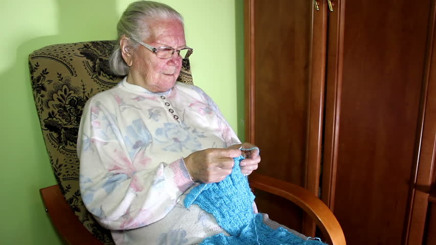 Old Lady Knitting Images : Grandmother knits a sweater sitting in front of