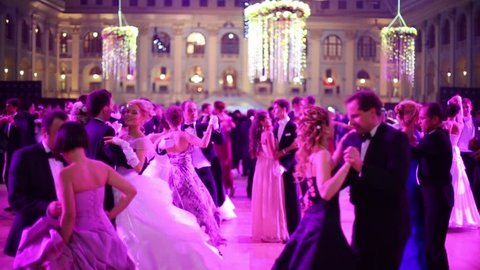 MOSCOW, RUSSIA - MAY 25, 2013: Waltzing pairs in pink light at 11th Viennese Ball in Gostiny Dvor