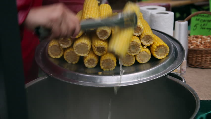 Buyers are waiting row until the corn vendor spreads butter baked hands remove boiled sweet corn cob from hot water street vendor food hd ccuart Choice Image