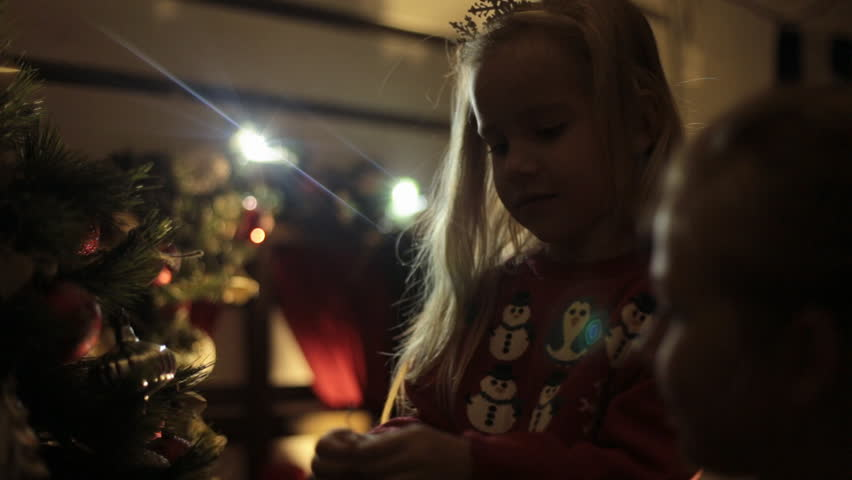 Little blond girl with long hair dressed in a red sweater with snowmens decorates Christmas tree with her mother in the dark   Shutterstock HD Video #8076367