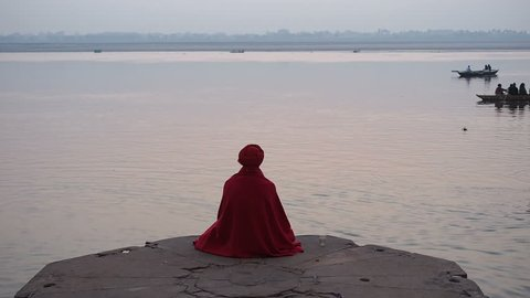 Varanasi, India - February 18: Sadhu (Indian holy man) sitting in meditation by the sacred Ganges river in Varanasi, Uttar Pradesh, India.