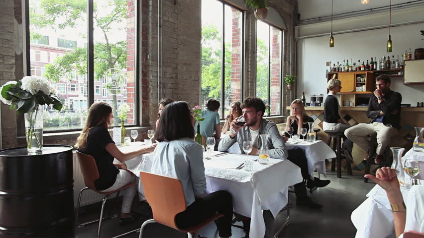 Many Young People Sitting and Talking in Stylish Restaurant