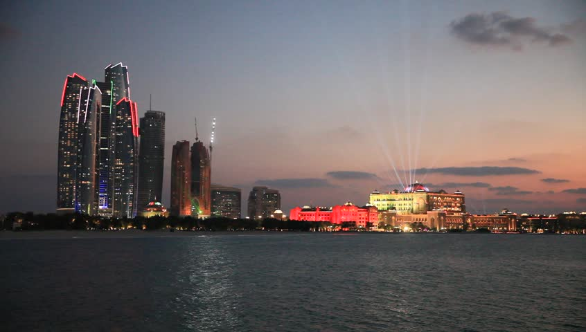 Abu Dhabi skyline at sunset with skyscrapers lit up for the 43rd National day