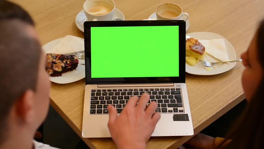 Computer (notebook) green screen - woman and man works on computer in cafe - coffee and cake | Shutterstock HD Video #8137621