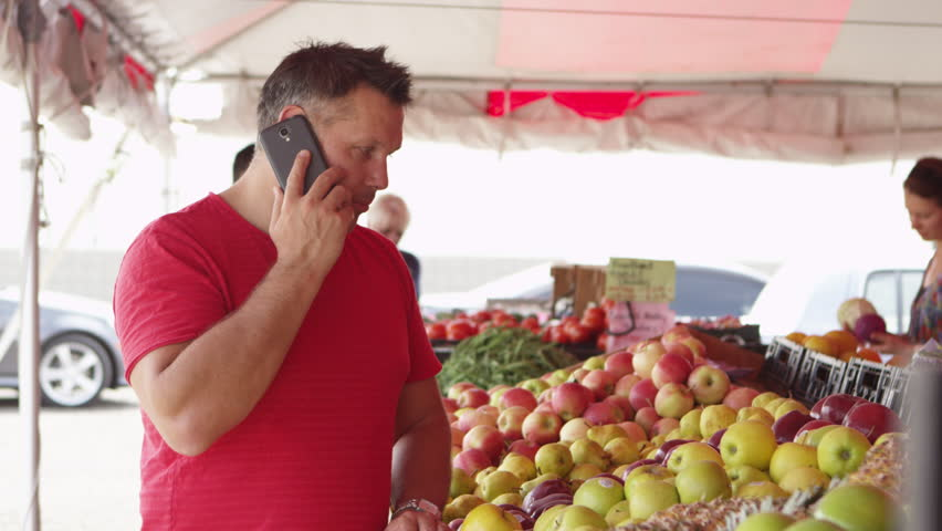 Man buying fresh fruits while on the cellphone | Shutterstock HD Video #8160748