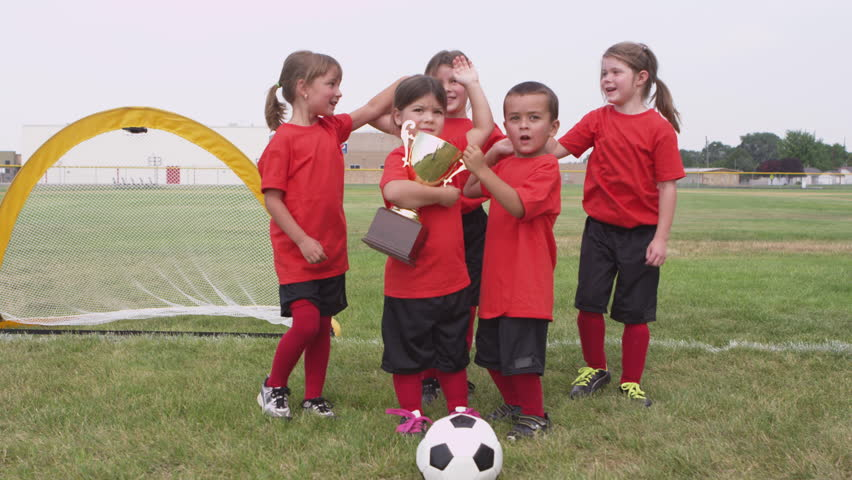 Children celebrating with trophy and soccer game