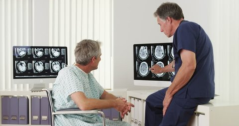 Mature doctor explaining xrays to disabled elderly patient