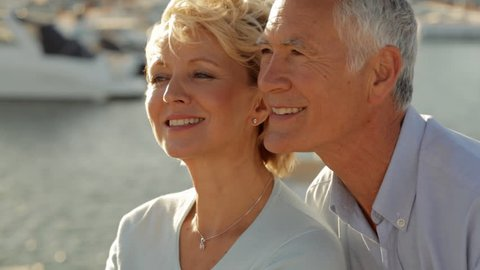 Head And Shoulders Shot Of Senior Couple Sitting Together By Marina In Sunset