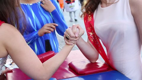 MOSCOW, RUSSIA - JUN 23, 2013: The girls graduates in beautiful dresses are arm wrestling on street at Graduate-2013.