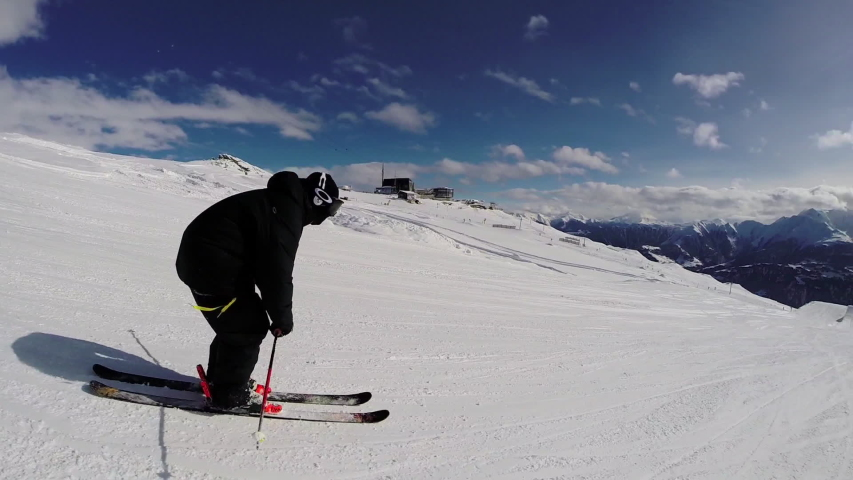 Slow motion rear view of skier carving down steep slope on