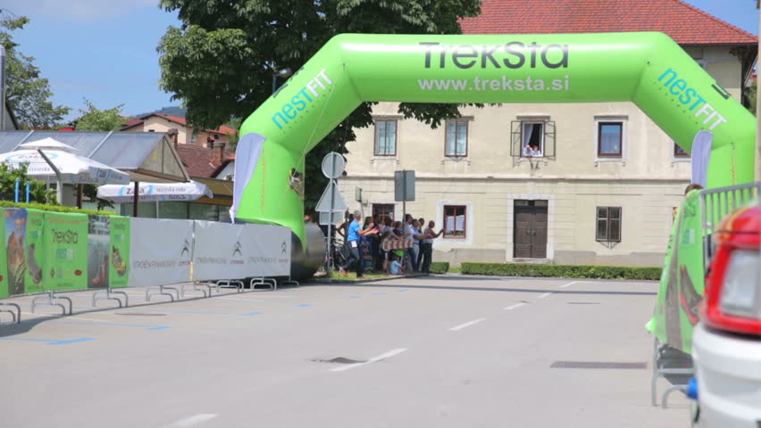 VRHNIKA, SLOVENIA - JUNE 2014: First bicycle competitor arrive through finish line. Wide shot of bicycle competition with finish line, people cheering and competitors arriving.