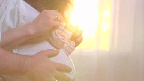 Pregnant Happy Woman holding Baby Shoes in her Hands. Mom and dad Expecting Baby. Pregnant Woman Belly. Pregnancy. Happy parents. Baby Shower. Slow motion 240 fps, high speed camera HD 1080p