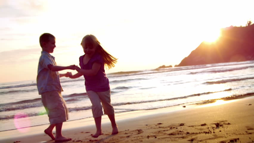 two children dance on the beach at sunset. lens flare.