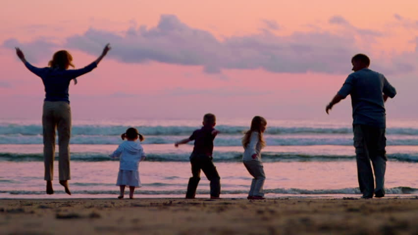 Three children and two adults jump on the beach at sunset.