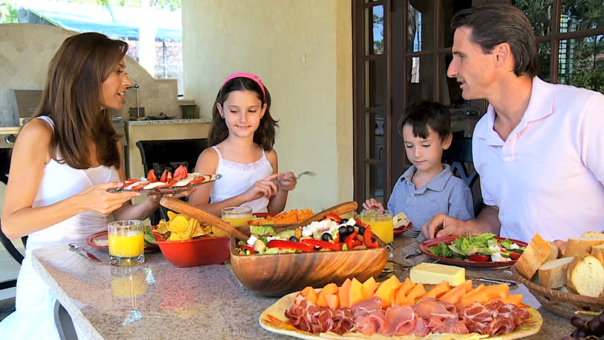 Attractive Caucasian family sitting at home sharing a healthy meal together 60FPS