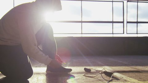 4K Hooded athlete tying his shoe laces and breathing heavily during his workout, shot on RED EPIC