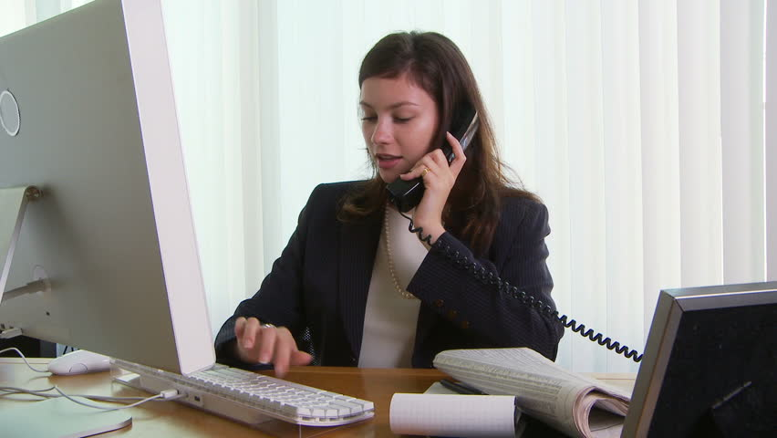 Young business woman at desk with phone and computer