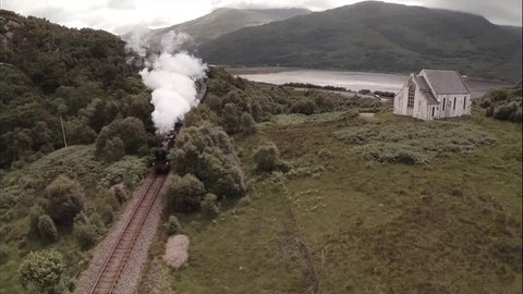 GLENFINNAN, SCOTLAND - JUNE 2014: Stunning aerial shot of the Jacobite Steam Train passing a small church set among stunning scenary in the Scottish highlands