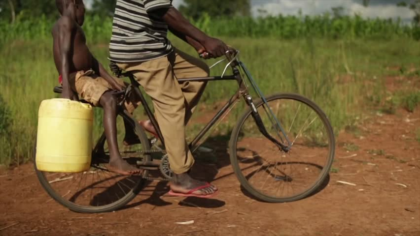 MOSHI, TANZANIA - MARCH 2013: African man on push bike with a child holding a water container