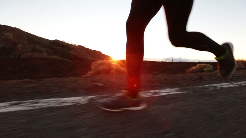 Running shoes and legs in action closeup. Male runner jogging on road. Man training at sunset at mountain road. Exercise and healthy lifestyle video.