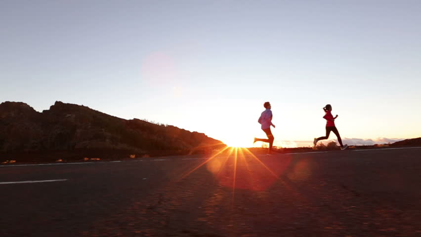 Sport running people running fast on road. Runners doing sprinting interval training on mountain road at sunset. Runner man and woman fitness athletes living healthy lifestyle exercising outdoors.