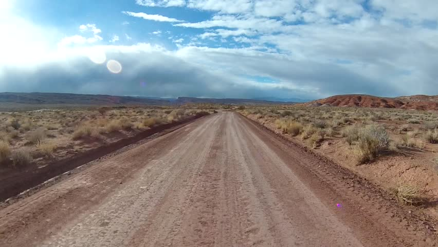 Off-road driving on high-desert road with winter storm in the distance. POV filmed in the desert southwest of St. George, UT along the Arizona border. #8444671