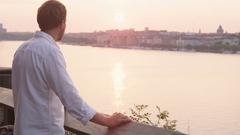 Man looking at sunset enjoying view. Young man relaxing enjoying calm serene moment in solitude in Stockholm, Sweden.