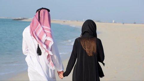 Middle Eastern couple walks alone the sea coast.