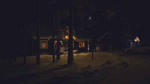 POV. Cozy wooden house in winter forest, at night, Finland.