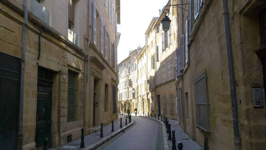 AIX EN PROVENCE, FRANCE - JANUARY 2015: People in the distance walking down a typical narrow street in the old town of Aix en Provence France.