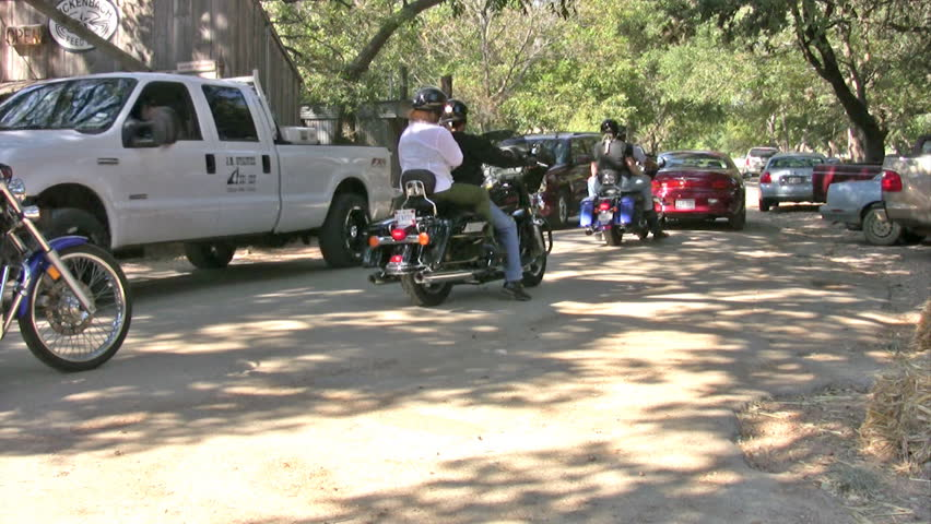 Video of motorcycles leaving Luckenbach Texas. Large group of motorcycle riders with Harley. Large oak trees and small country store and environment.
